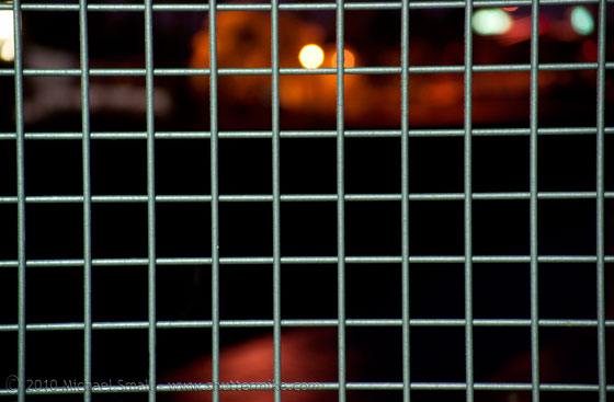 Photo of the night sky through a fence