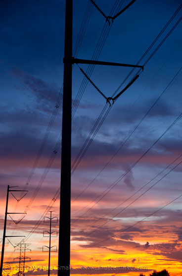 Photo of telephone poles set against a sunset