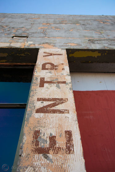 Photo of a faded and warn entry sign painted on a concrete wall