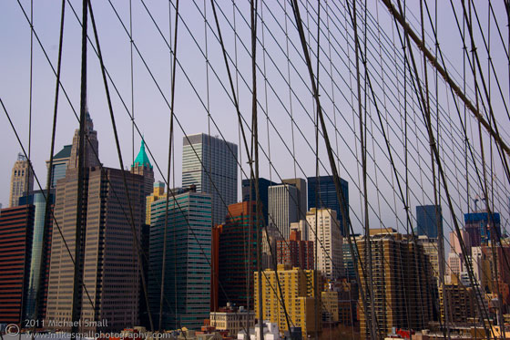 Photo of downtown New York City seen through the Brooklyn Bridge suspension wires
