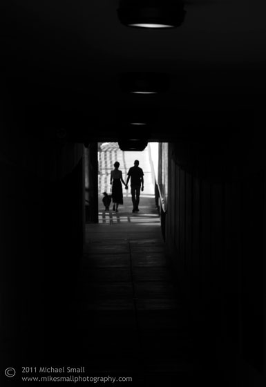 Photo of a couple holding hands emerging out of a dark tunnel