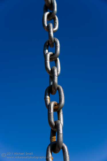Photo of a section of chain against a blue sky