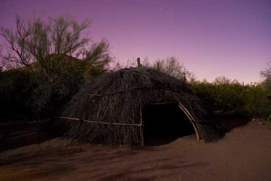 Photo of a Native American dwelling at night.