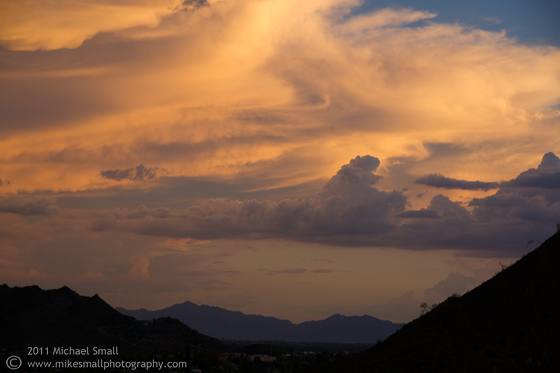Photo of the sun setting through Phoenix storm clouds