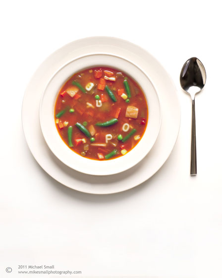 Photograph of a bowl of vegetable alphabet soup in a white bowl
