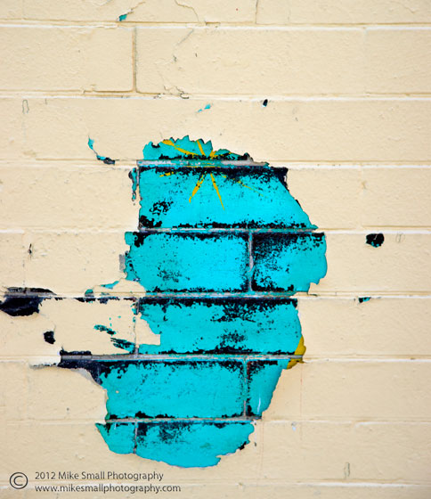 Photo of peeling paint on a brick wall